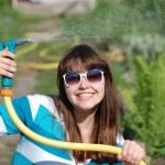 vacker ung flicka vattning trädgård — Stockfoto #11608758