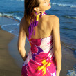 Beautiful woman posing on the beach with colourful dress — Stock Photo