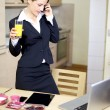 Businesswoman talking on the phone while drinking orange juice — Stock Photo