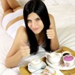 Beautiful girl thumbs up during breakfast in bed — Stock Photo