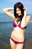 Beautiful female model posing on the beach in bikini — Stock Photo