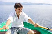 Happy handsome man rowing on a lake — Stock Photo