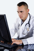 Male Doctor typing on computer — Stock Photo