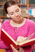 Dívka v knihovně čtení knihy — Stock fotografie