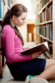 Girl in the library reading book — Stock Photo