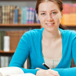 Girl studying in library - Stockfoto
