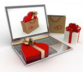 Box as heart form with a gold bow lies on a laptop — Stock Photo