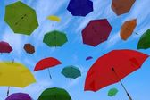 Flying of multicoloured umbrellas — Stock Photo