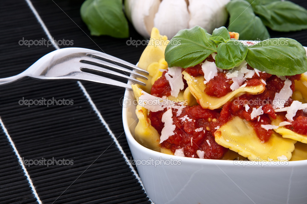 Portion of Raviolis with tomato sauce and Parmesan Cheese in a bowl with raw ingredients in the background on a black tablecloth — Stock Photo #10965909