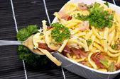 Käse-spätzle auf schwarze tischdecke — Stockfoto
