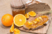 Bread with Orange Jam (rustic background) — Stock Photo