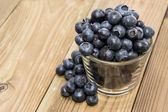 Blueberries in a glass on wood — Stock Photo