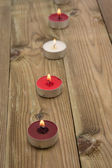 A line of burning candles in daylight — Stock Photo