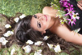 The young woman lies in the petals of flowers — Stock Photo