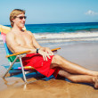 Stock Photo: Young Man Relaxing at the Beach