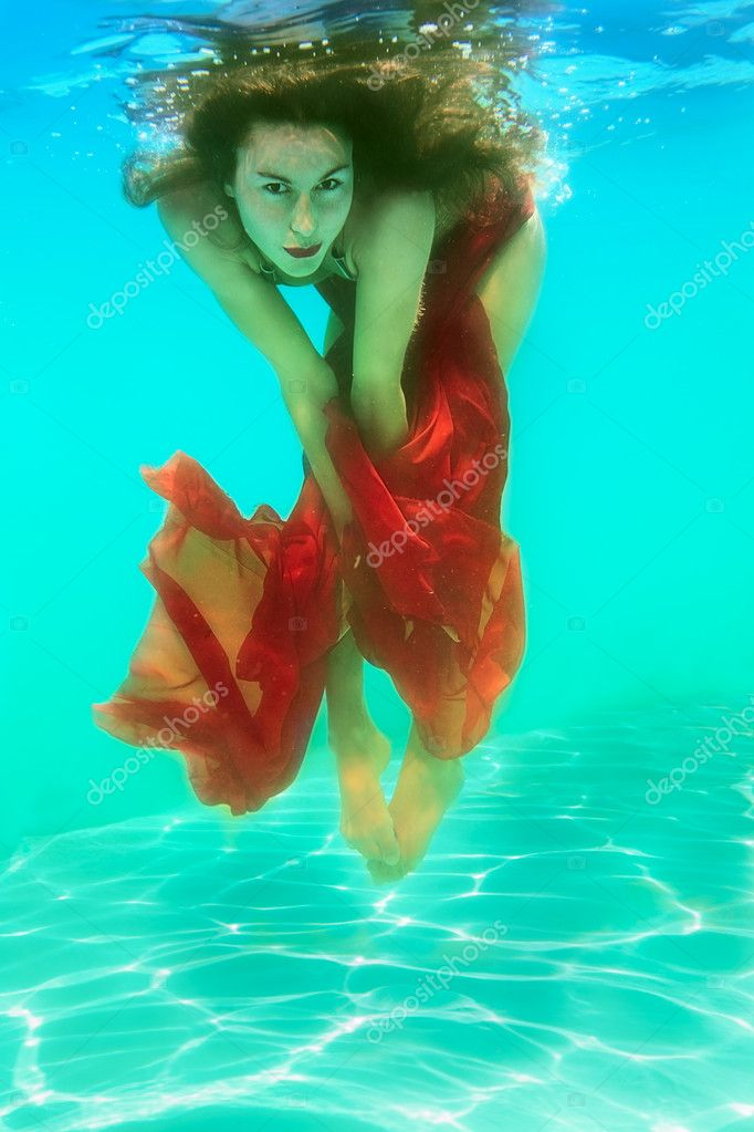Girl under the water holding a bright red fabric — Stock Photo #12056042