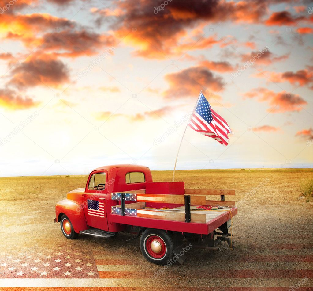Red vintage pick up truck with American flag in wide open country side with dramatic sunset cloudscape and US flag on ground — Stock Photo #11406532