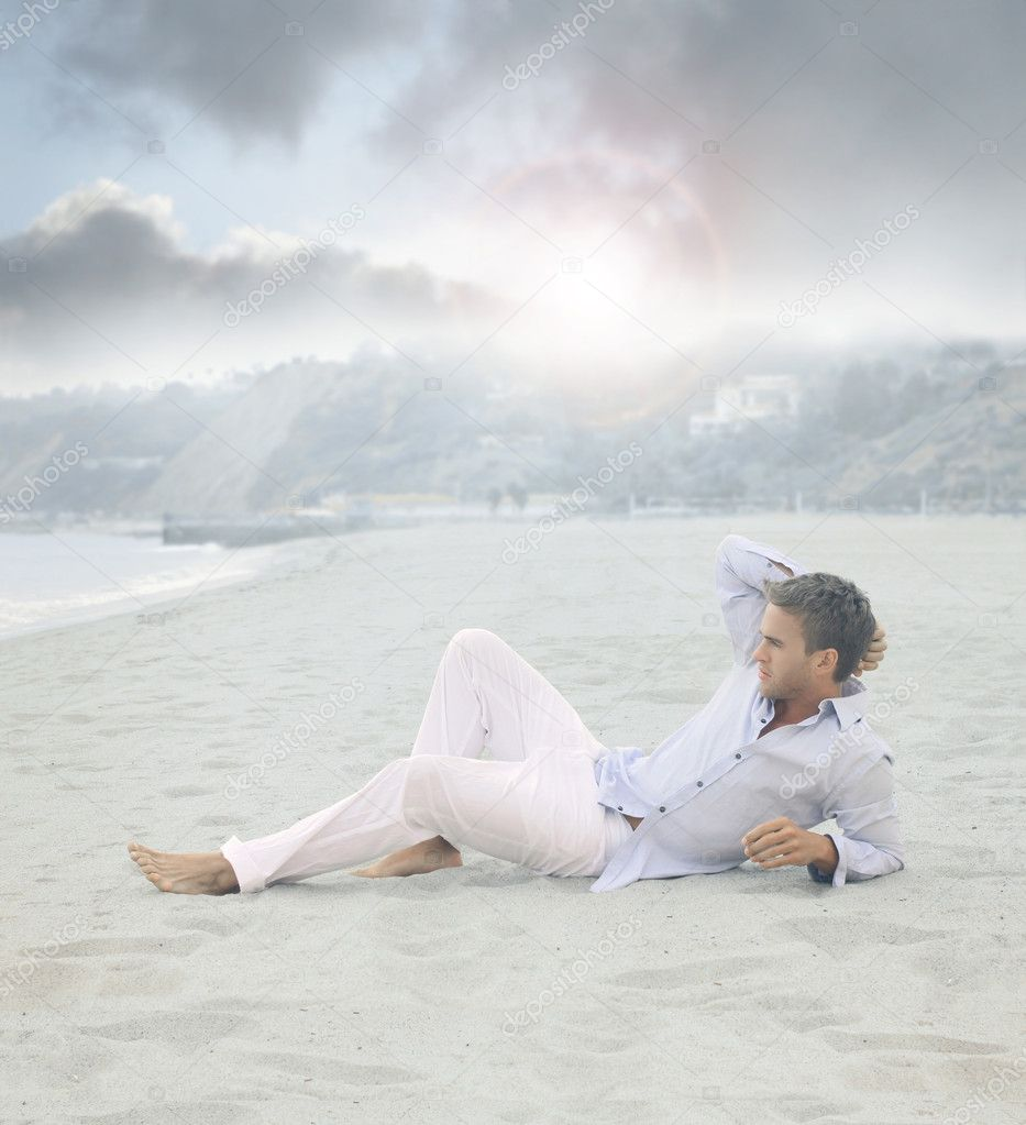Young relaxed man laying on beach in calm blue morning light  Stock Photo #11538364