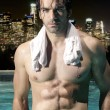 Sexy man in pool at night — Stock Photo