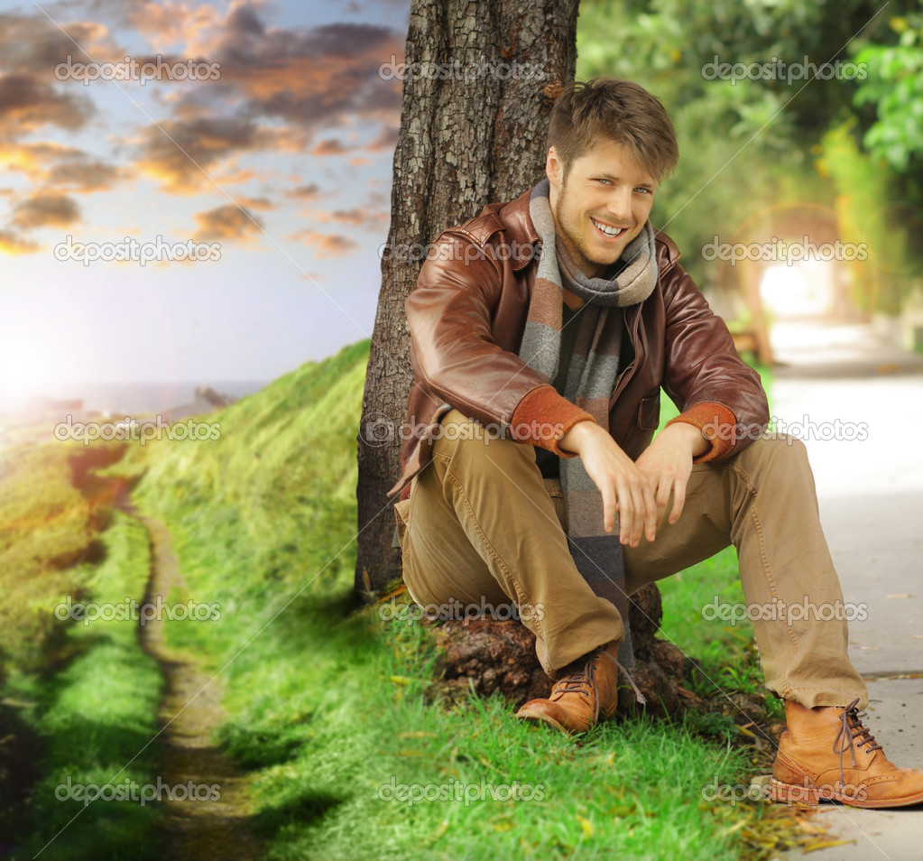 Young Stylish Happy Man In Autumn Clothing Leaning Against Tree