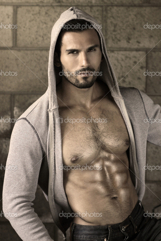Young handsome macho man with open jacket revealing muscular chest and abs — Stock Photo #12312500