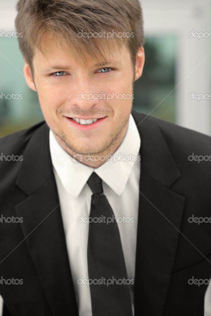 Closeup of a young businessman smiling — Stockfoto #12383828