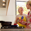 Stock Photo: Mom and daughter cooking in home kitchen
