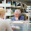 Senior man studying among young in library — Stockfoto