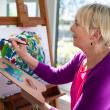 Happy elderly woman painting for fun at home — Photo