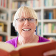 Happy senior woman with glasses reading book at home — Stock Photo