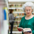 Senior woman reading and choosing book in library — Stock Photo
