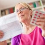 Senior woman with medication pills and prescription — Stock Photo