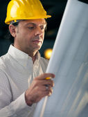 Adult businessman working as engineer holding blueprints — Stock Photo