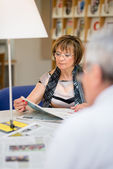 Old woman reading newspaper with husband in library — Stock Photo