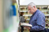 Old man reading and choosing book in library — Stock Photo