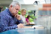 Uomo anziano studiando tra giovani in biblioteca — Foto Stock
