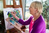 Heureuse femme âgée, peinture pour le plaisir à la maison — Photo