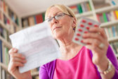 Senior woman with medication pills and prescription — Stock Photo