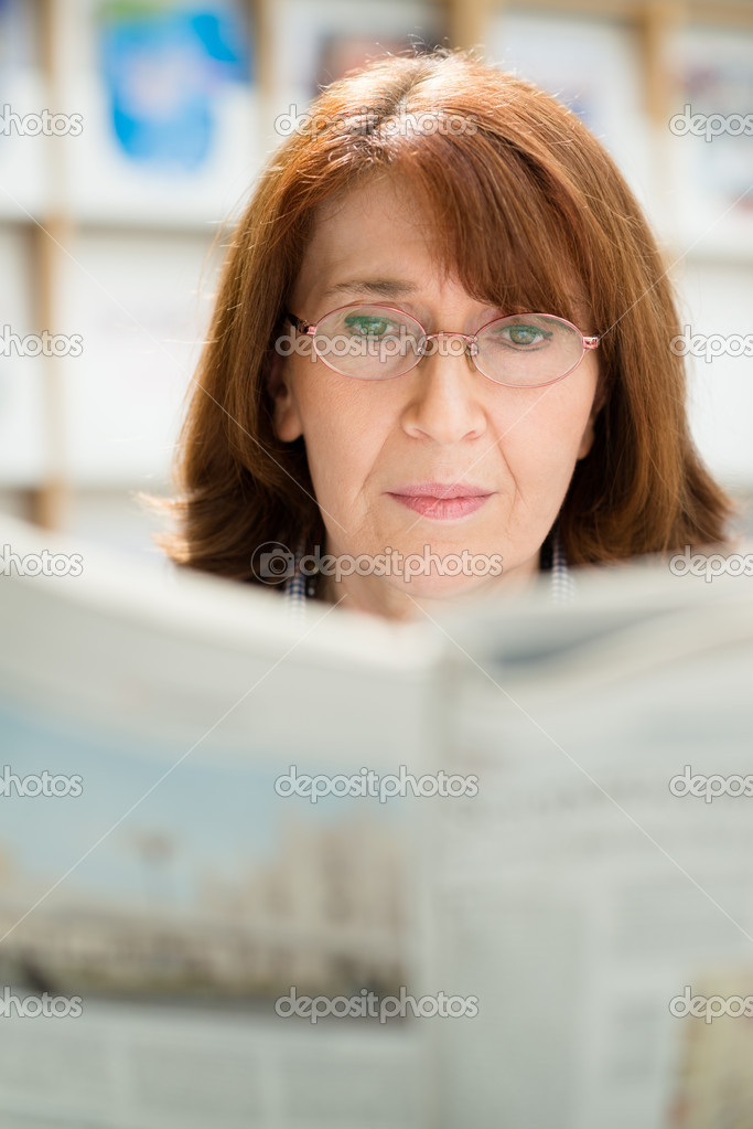 Portrait of middle aged woman with eyeglasses reading paper in library — Stock Photo #11084398