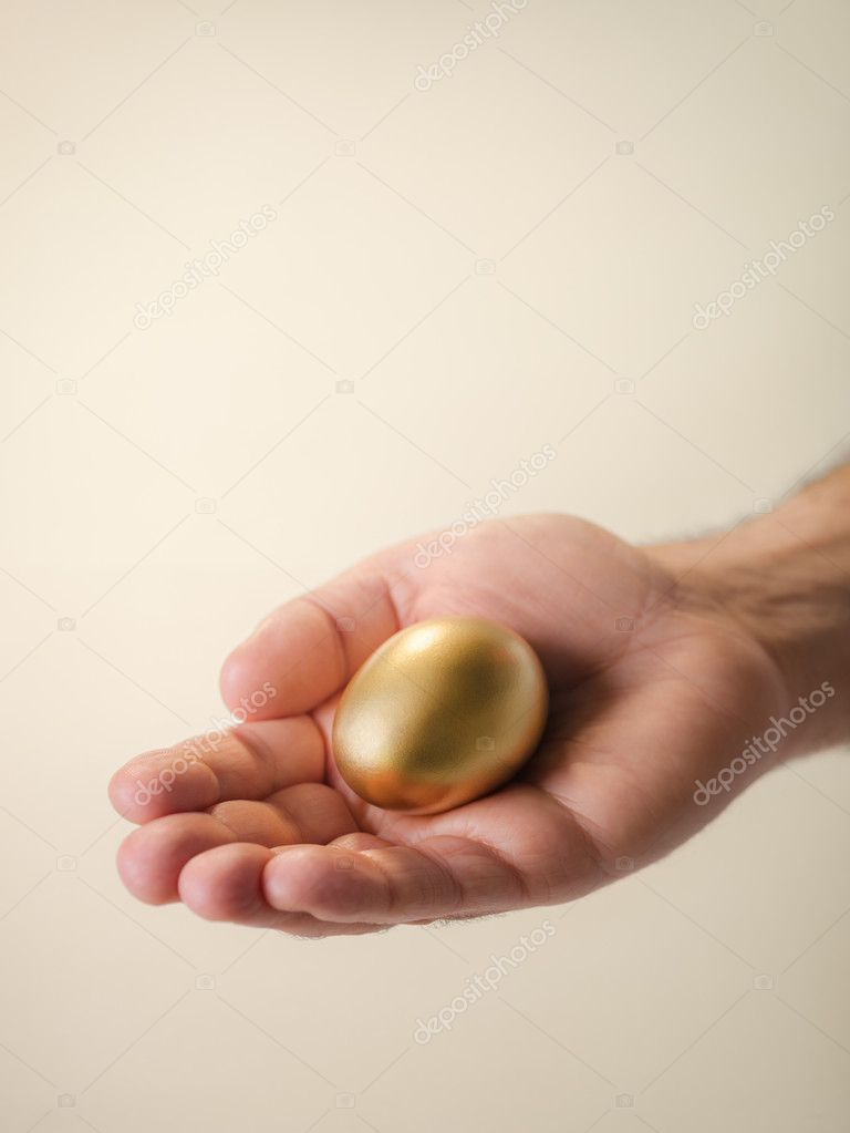 Man showing golden egg and holding it in hand. Concept of securing savings, money, precious and valuable things, prizes. Copy space — Stock Photo #11084643