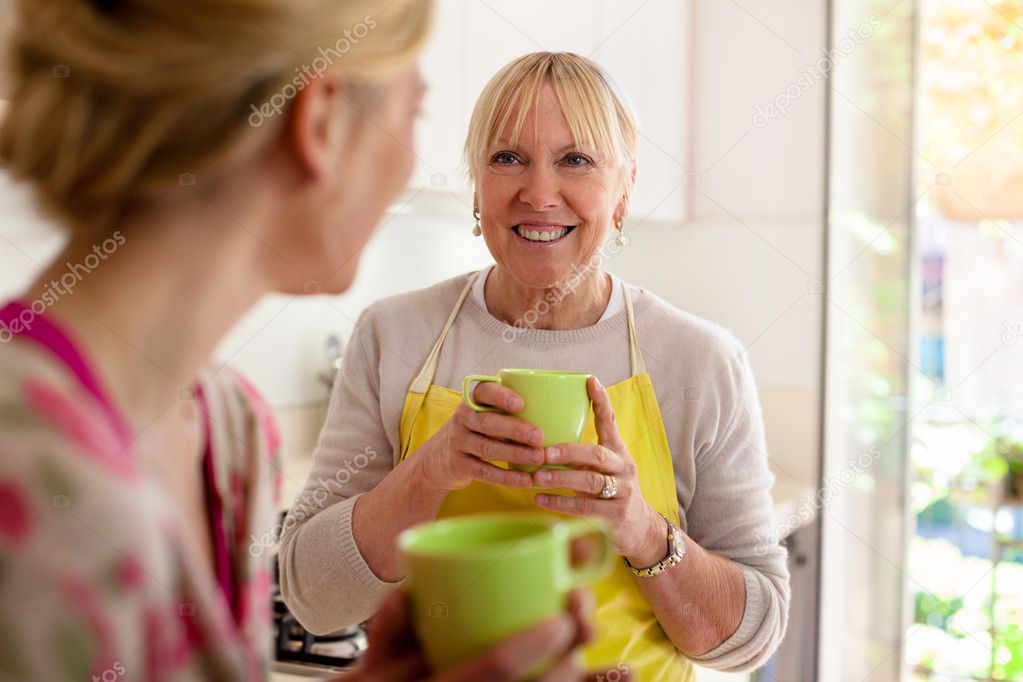 Happy women in home kitchen: mom and daughter talking and drinking a cup of tea  Stock Photo #11084743
