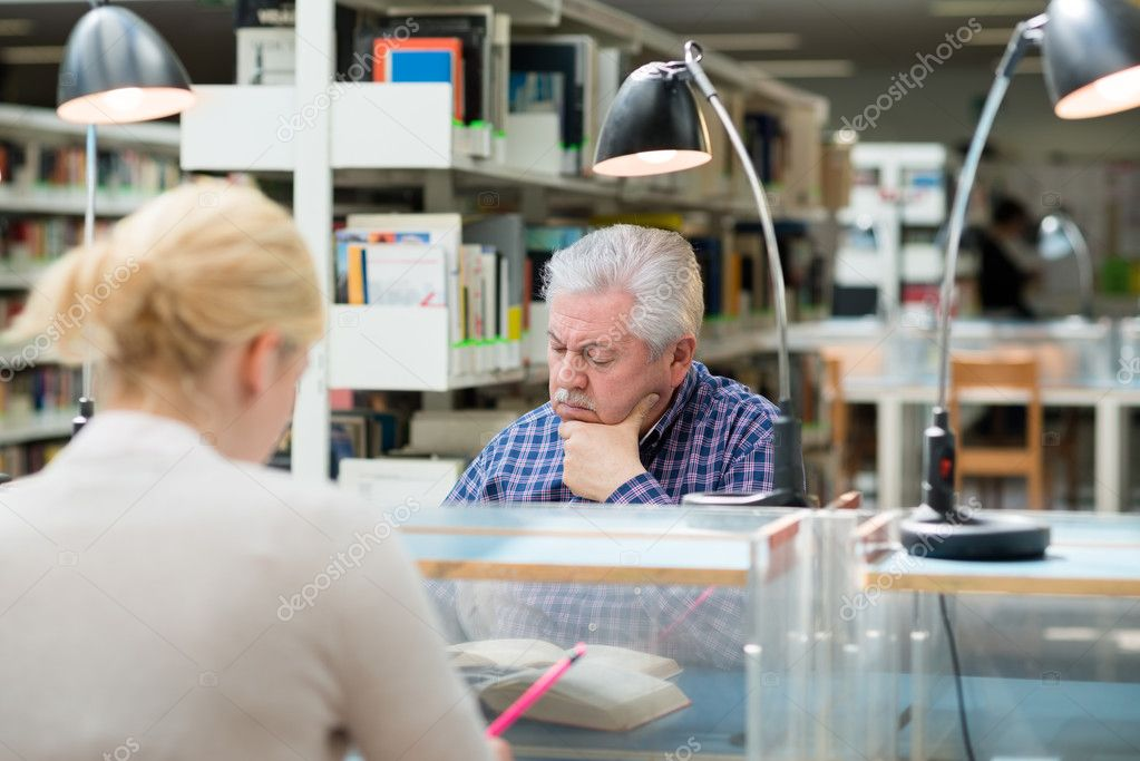 Elderly man studying among young college students in library and taking notes — Stock Photo #11085037