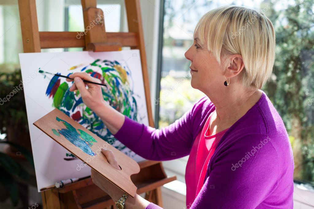 Happy retired woman painting on canvas for fun at home — Stock Photo #11085435