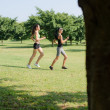 Sport with two young women jogging in city park — Stock Photo
