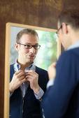 Hombre joven de vestirse y mirando en el espejo — Foto de Stock