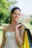 Happy young woman smiling with shopping bags — Stock Photo