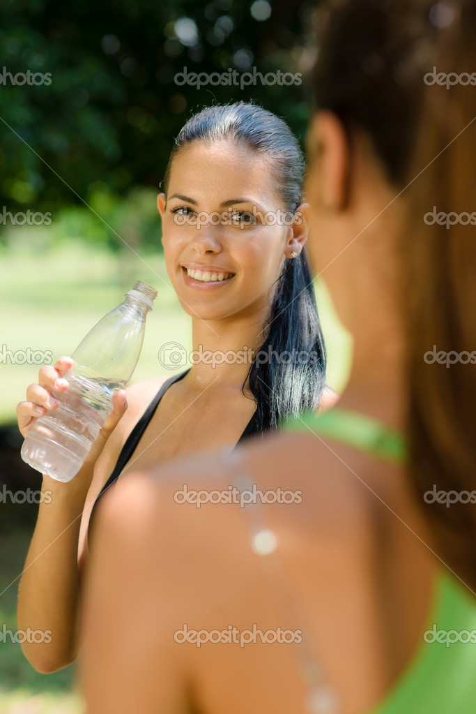 Two female friends relax and drinking water after running in city park — Stock Photo #11433970