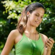 Woman with mp3 player listening to music and jogging - Stock Photo