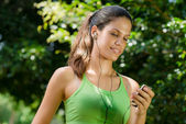 Woman with mp3 player listening to music and jogging — Stock Photo