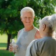 Seniors drinking water after fitness in park — Stock Photo